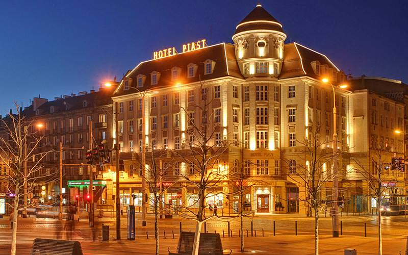 The exterior of Hotel Piast lit up at night