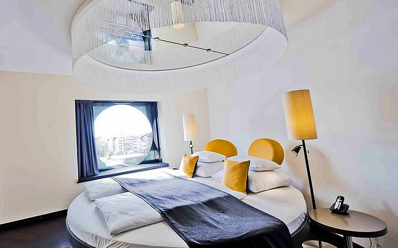 A circular double bed topped with a grey throw and yellow cushions, underneath a large chandelier