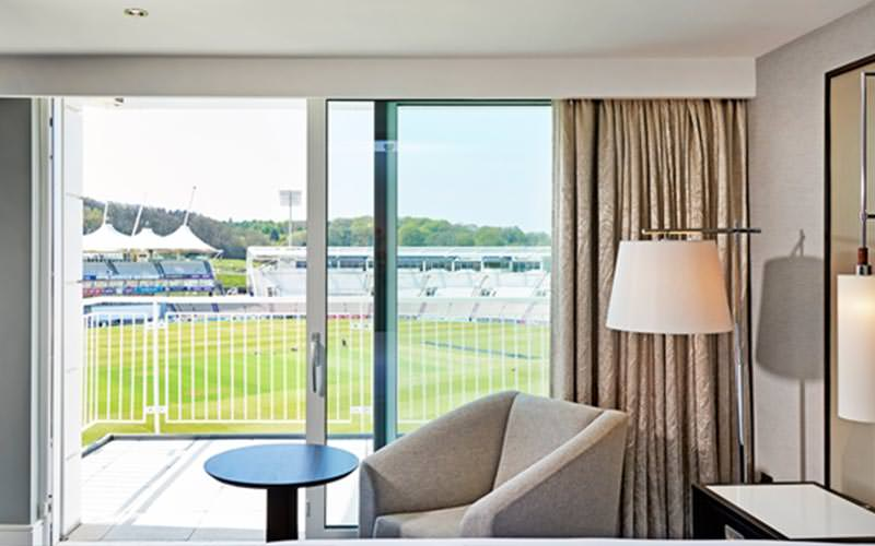 A table and chair in front of floor to ceiling windows over the cricket stadium
