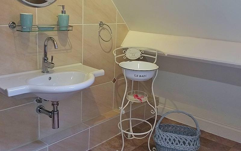 Bathroom sink, white shelf and blue wicker basket