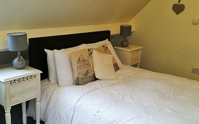 A white double bed with cushions on top, in between two bedside tables