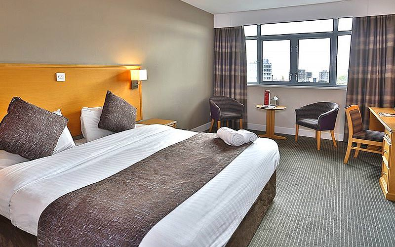 A double bed in a room with towels on the end of the bed, and some tall buildings out of the window