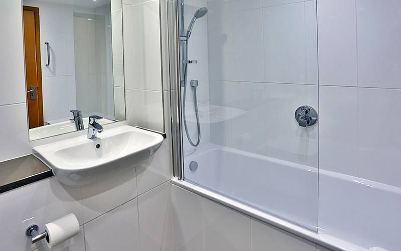 A white bathroom with silver trimmings