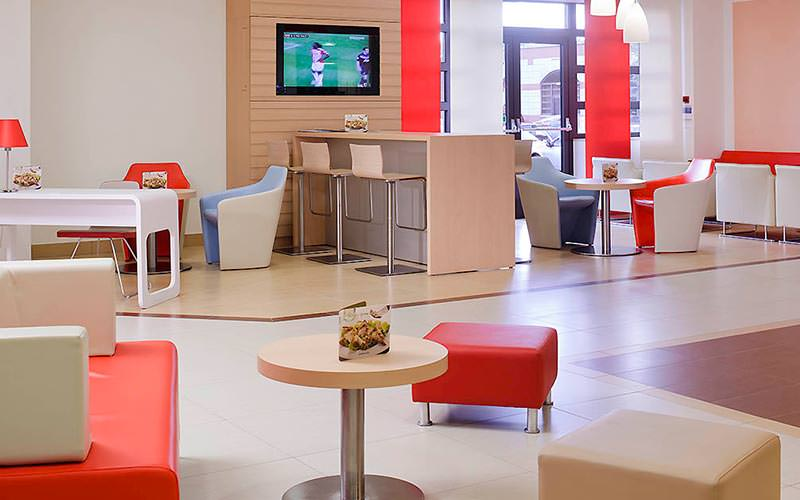A seating area with football playing on the TV in the background
