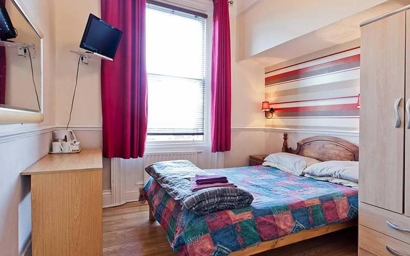 A double bed with colourful bedding, facing drawers and a TV on the wall, with a wardrobe in the foreground