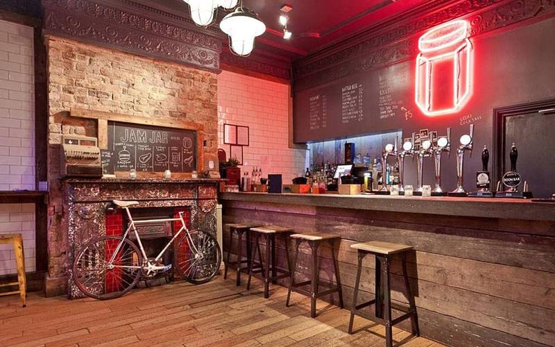 Bar stools, a bike and an old fireplace in front of the bar at New George Hotel