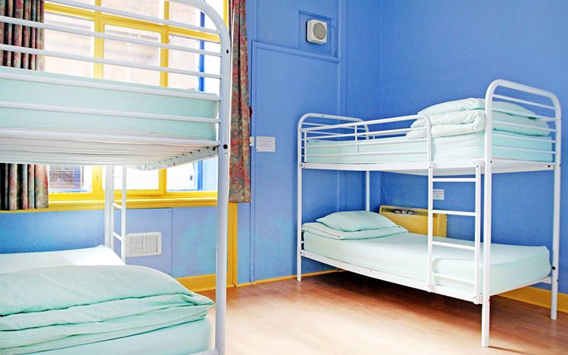 A dorm room with two bunk beds and bright blue walls