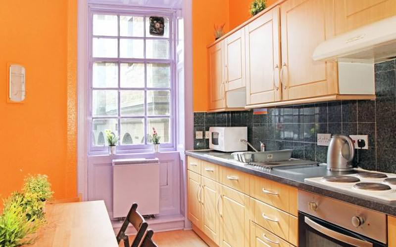 A quaint kitchen area with orange and purple decor