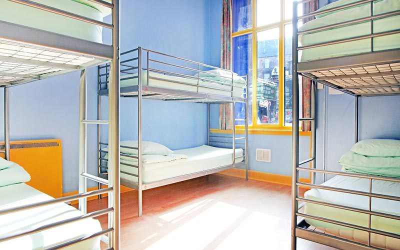Three bunk beds in a dormitory room