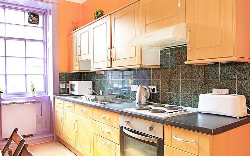 A quaint kitchen area with wooden furniture and purple and orange decor