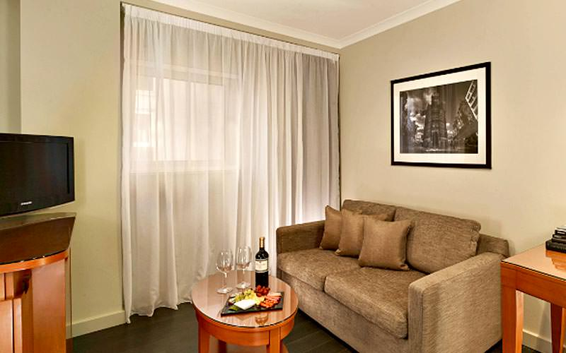 A room with a TV and sofa, as well as a bottle of red wine and two glasses on the table
