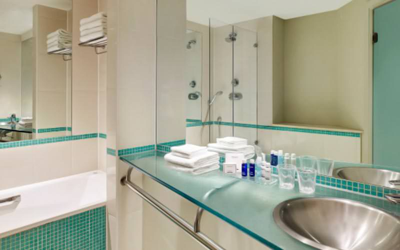 A teal and white bathroom with towels and toiletries lined up on the side of the sink