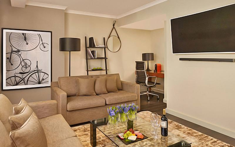 A living room area with a huge TV mounted on the wall, two sofas and a poster of lots of bicycle wheels