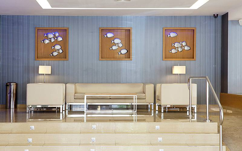 Cream sofas, chairs and a coffee table underneath three images of silver fish