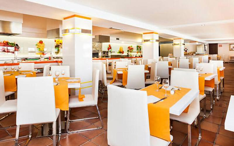 Tables with yellow table runners, and white chairs in the hotel restaurant at Globales Cortijo Blanco