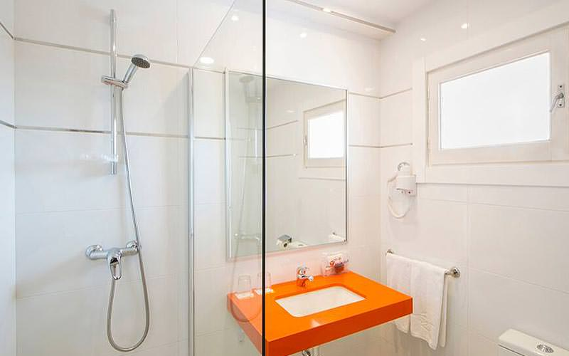 A white bathroom with a shower on the side, and orange sink
