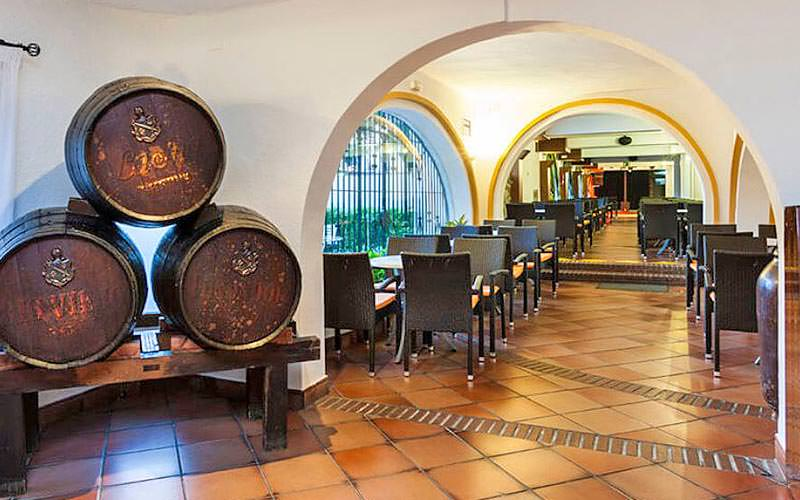 Three barrels in the arched entrance to the hotel restaurant at Globales Cortijo Blanco, with tables and chairs in the background