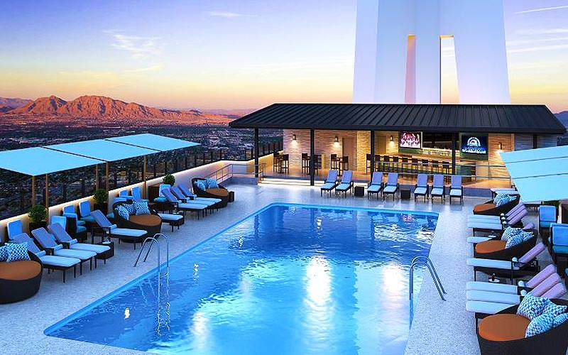 An outdoor swimming pool with expansive desert views and sun loungers
