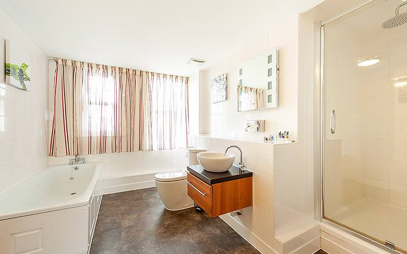 A fresh looking bathroom with cream curtains and a wooden part under the bowl of the sink
