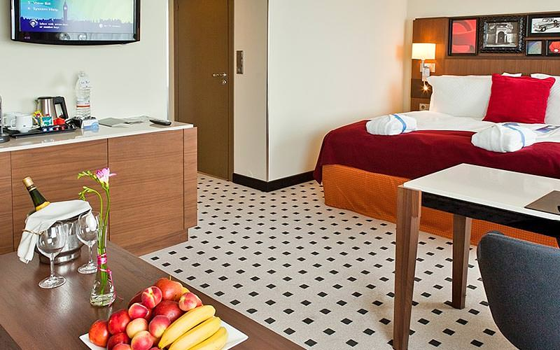 A plush double room in Radisson Blu Hotel Latvia, with fruit and wine in the foreground