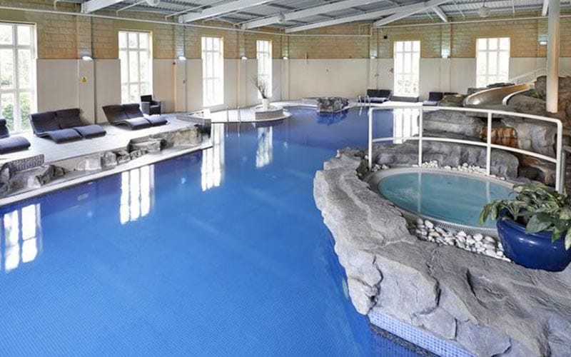 Indoor pool, with loungers around one side, at Slaley Hall