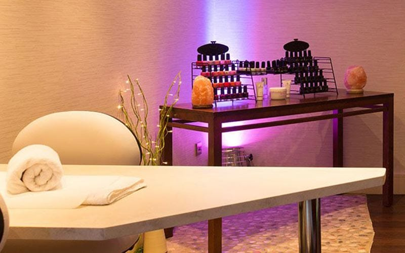 Lots of nail varnish bottles lined up on a desk with a treatment table in the foreground
