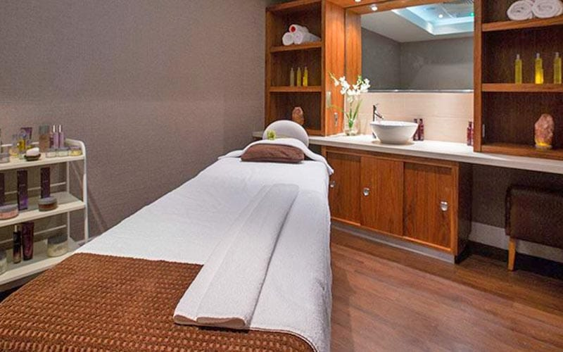 A treatment room with a bed, sink and beauty product trolley in it