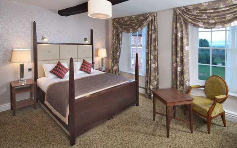 A bedroom with a four poster bed and two large windows