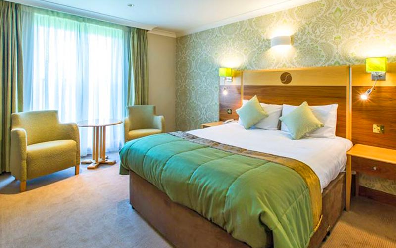 A double bed with green and white bedding in The Hampshire Court Hotel