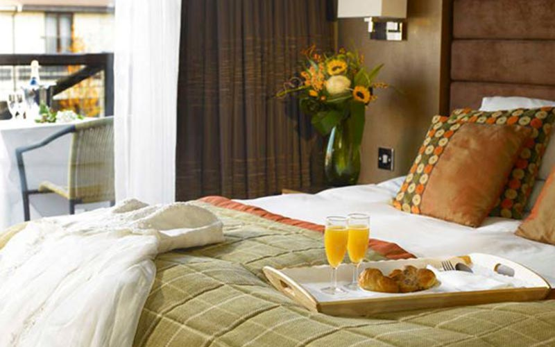 Some orange juice and croissants on the bed in The Hampshire Court Hotel