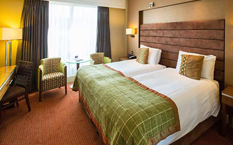 Two single beds in a room with a green and brown colour scheme