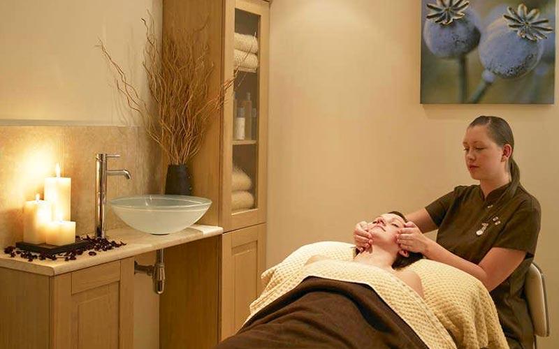 A woman receiving a facial in a spa