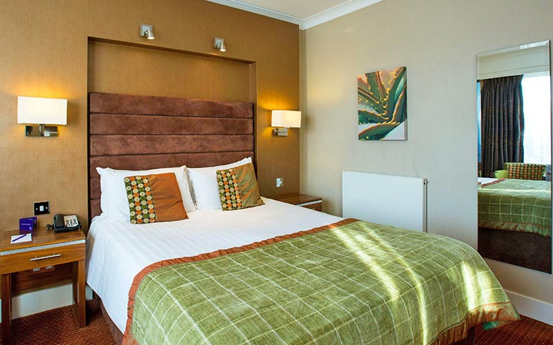 A double room in The Hampshire Court Hotel with a green and orange colour scheme and a mirror or the wall
