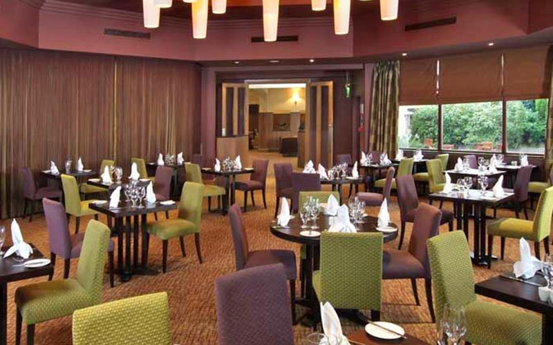 A large area with lots of tables and chairs in Westerwood Hotel and Golf Resort