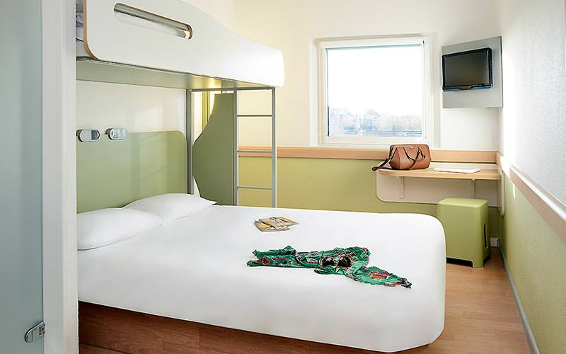 A double bed in a lime coloured room