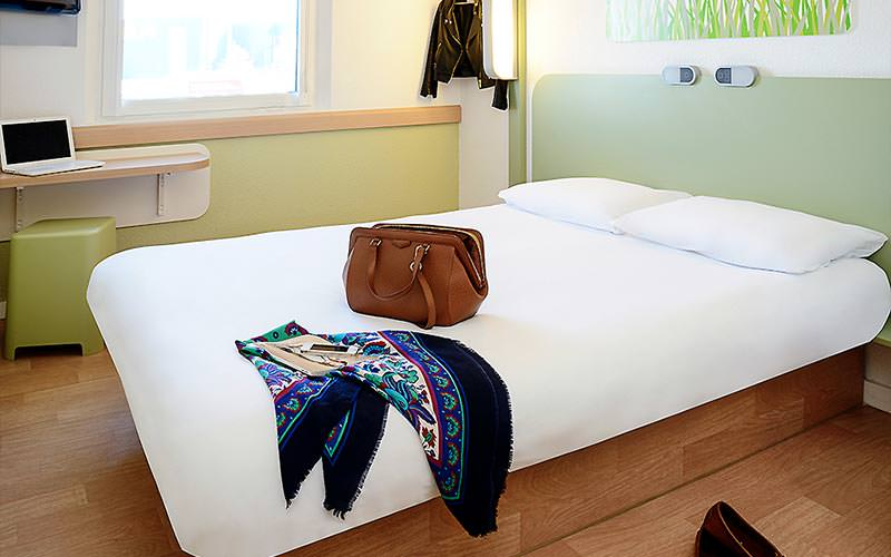 A fresh green and white bedroom with a bag and scarf lying out on the bed