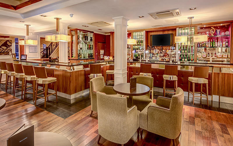 The bar area in Hilton Edinburgh Grosvenor, with wooden floorboards and a fully stocked bar
