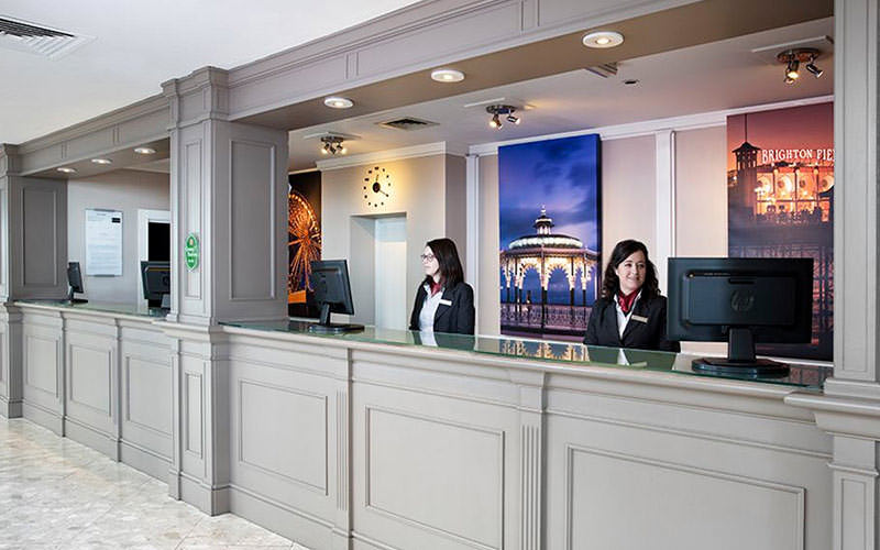 Two women behind a reception desk at Jurys Inn Waterfront, Brighton
