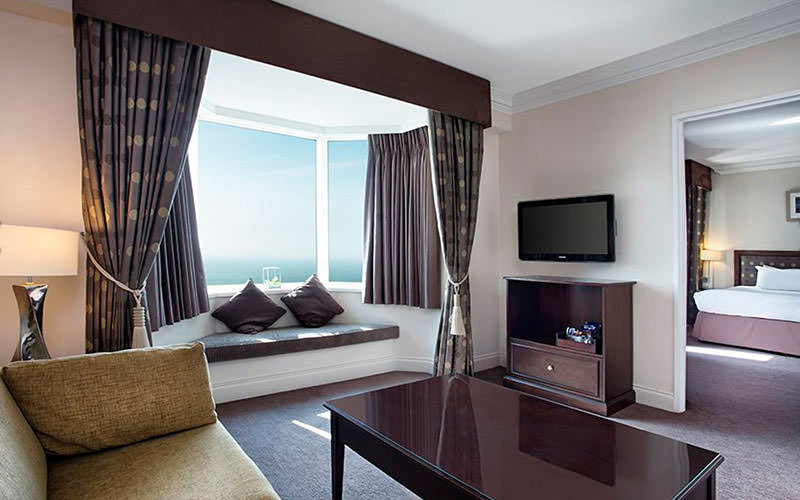 A hotel suite featuring a large sofa, plasma TV, coffee table and seating under the window