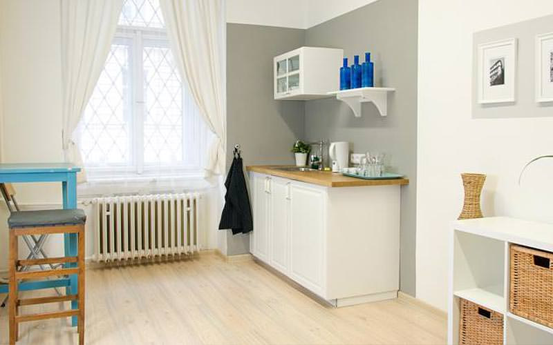 A white kitchenette facing a blue table and stool