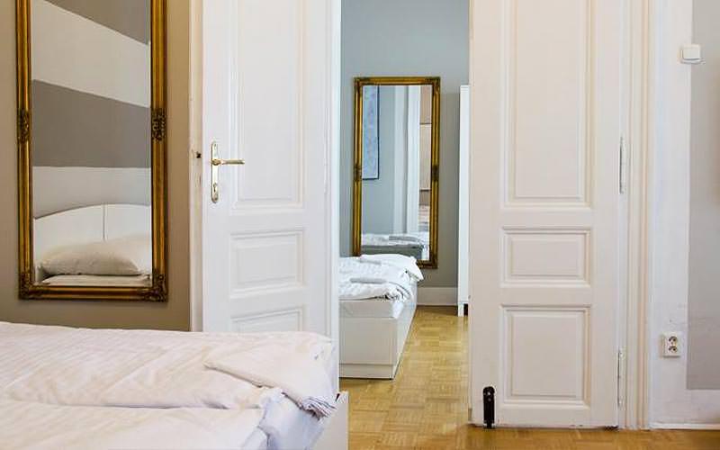 A double bed an mirror visible through an open door in an apartment