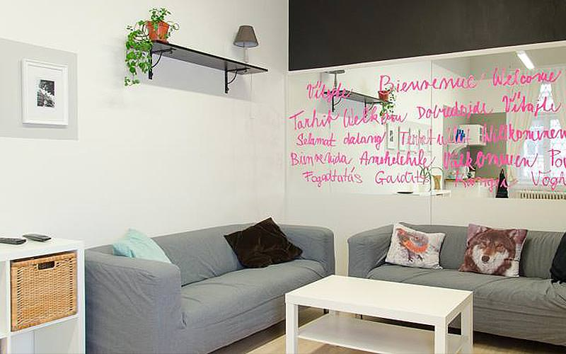 Two grey sofas around a white coffee table, with pink writing on a wall