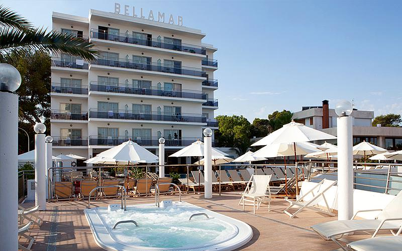 Exterior of Bellamar Hotel, with an outdoor pool and sun loungers, during the day