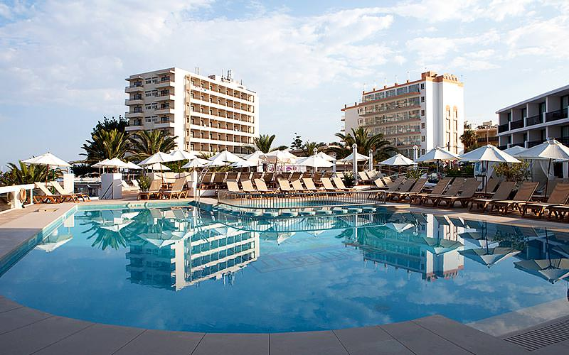 An outdoor pool and sun loungers in front of the Bellamar Hotel, during the day