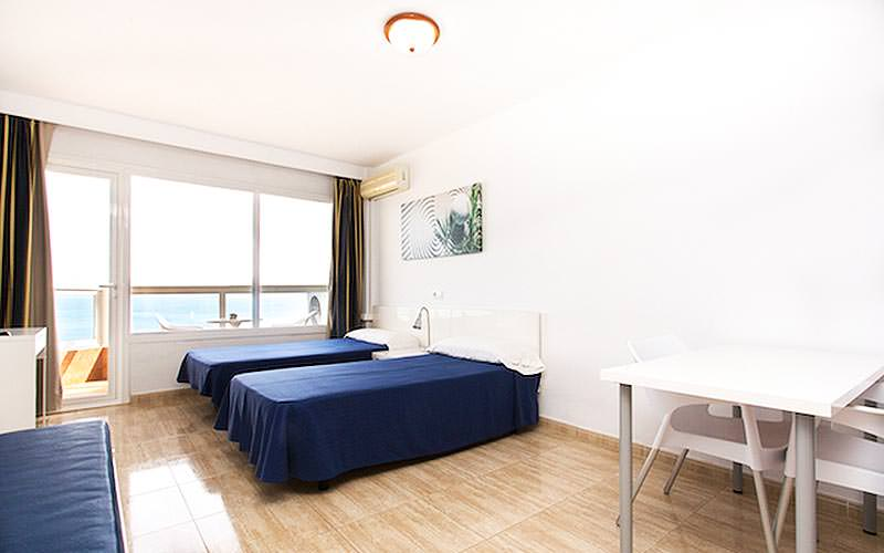 Three single beds with blue bedding, in a hotel room, with a white table and chairs in the foreground