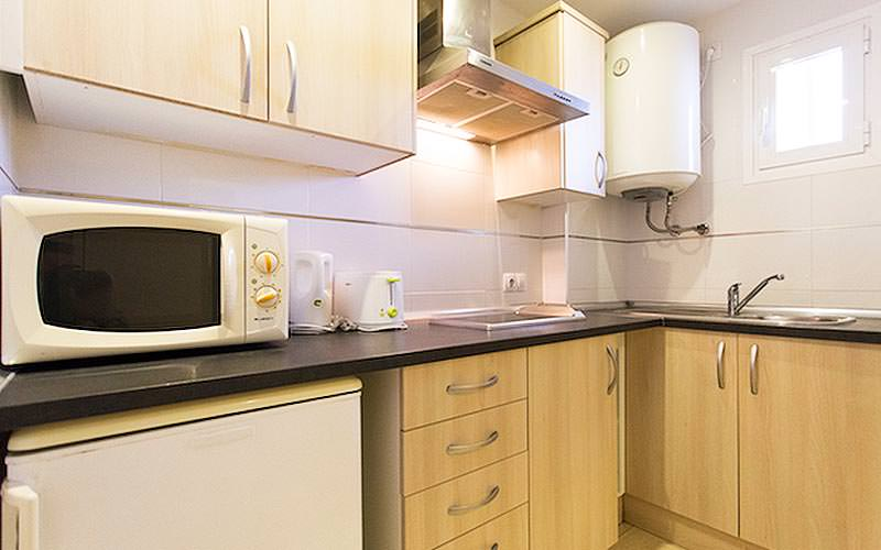 A light wood kitchenetter with appliances on the counters