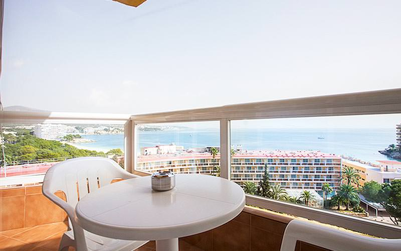 A white table and two chairs on a balcony, with the coast in the background