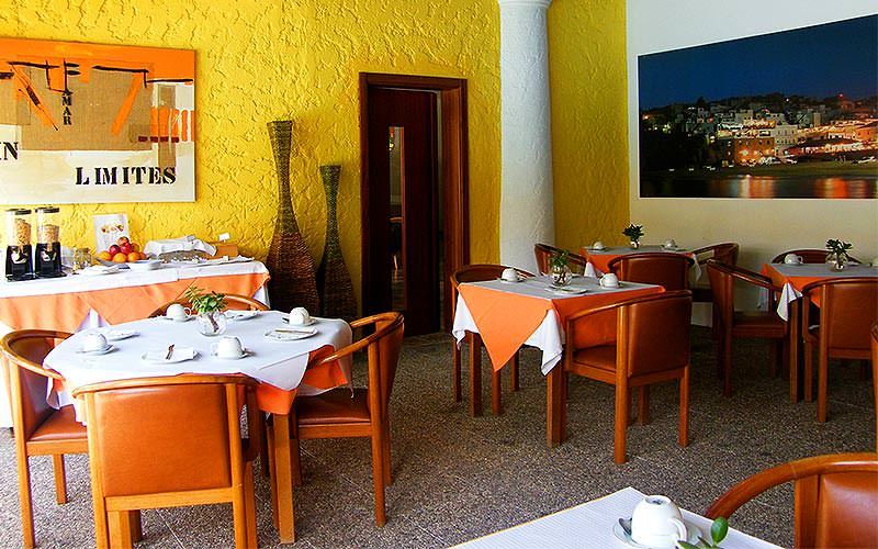 Tables and chairs set for dinner in the yellow Solar De Sao Joao hotel restaurant