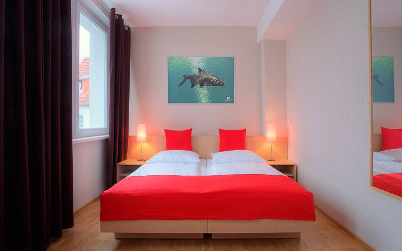 A double room with bright red and white bedding on the double bed, and a painting of a shark on the wall