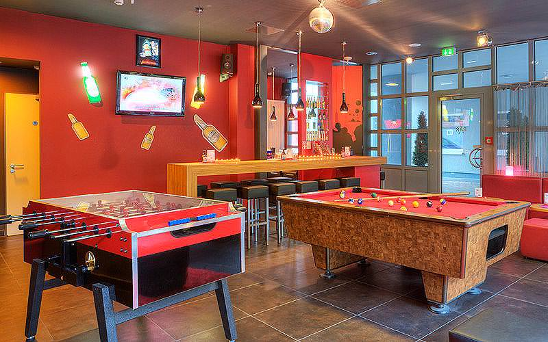 The games room within Meininger Hotel Hamburg, with a pool table and a table football table